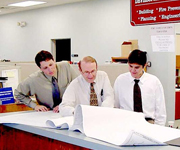 3 men looking over documents in an office