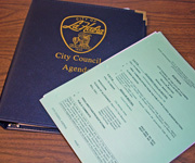 City Council Agenda notebook with papers on top